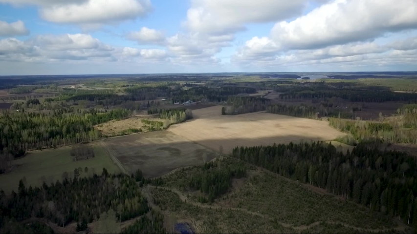 Aerial drone shot of forest and fields. Flying over Finland landscape.   Shutterstock HD Video #1032354779