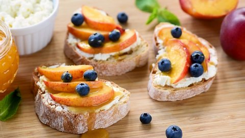 Tasty fruit bruschetta with ricotta cheese, peach, blueberries and honey on wooden serving board. Healthy appetizer, breakfast or snack
