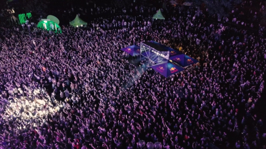 KYIV-25 MAY,2019: Aerial drone footage of summer music festival crowd partying to popular edm dj set on dance floor.Radio Day Festival event shot from above view flying video camera at night