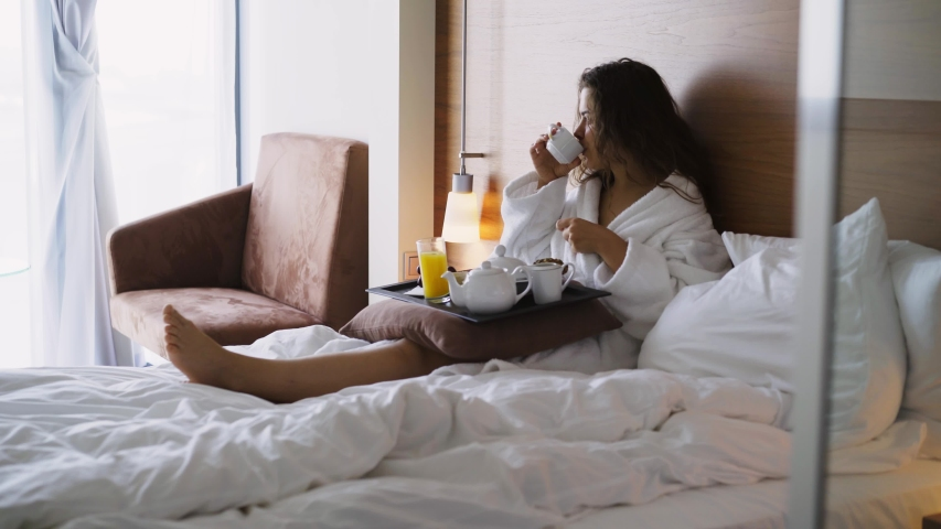 Girl in light hotel apartment with full length windows. Side view woman in white bathrobe lying in bed and have breakfast on small table-tray, enjoying coffee at morning time   Shutterstock HD Video #1032560549