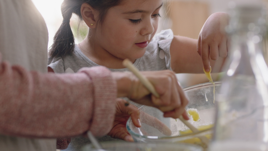 Little girl helping mother bake in kitchen mixing ingredients baking cookies preparing recipe at home with mom teaching her daughter on weekend | Shutterstock HD Video #1032607139