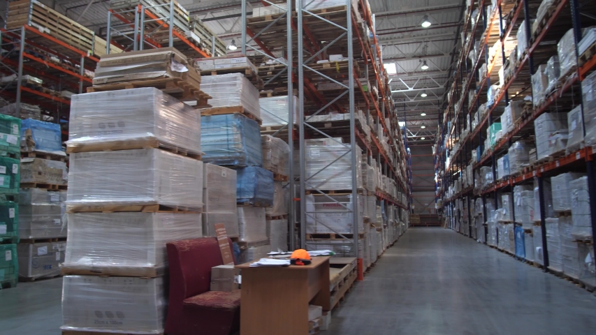 Huge logistic warehouse. Panorama between the rows with shelves. The warehouse is filled with products in boxes.   Shutterstock HD Video #1032609419