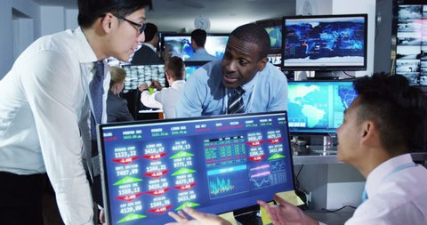 4K Team of financial brokers watching the world markets in a busy trading room