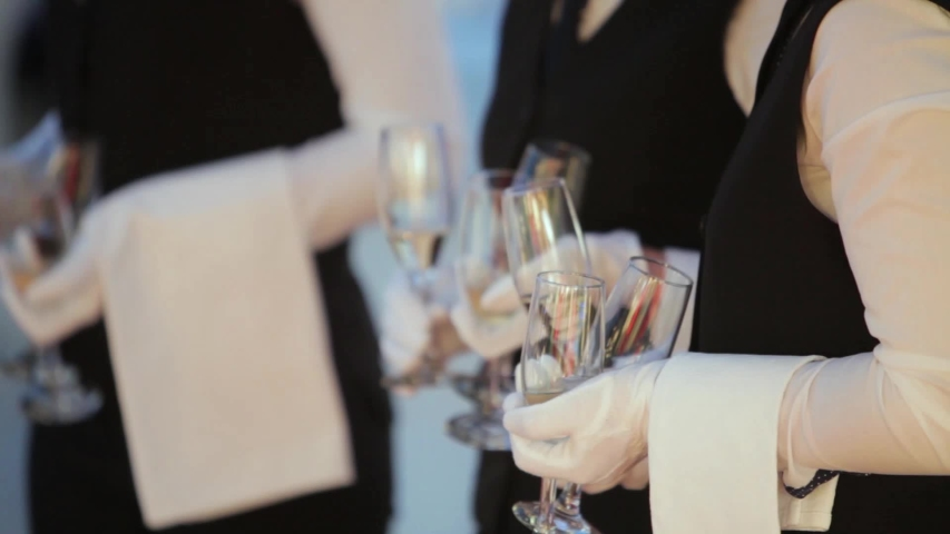 Row of waiters with white gloves and tuxedo serving the high class people | Shutterstock HD Video #1032674999