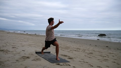 A man doing a yoga on the beach to improve mental and physical health in slow motion.