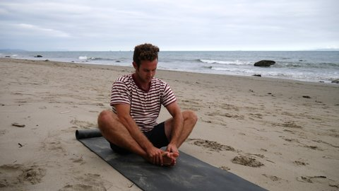 A man stretching on a yoga mat before practicing poses on the beach with ocean waves in California SLOW MOTION.