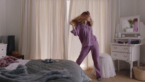 happy woman dancing in bedroom enjoying weekend morning having fun celebrating carefree lifestyle wearing pajamas at home