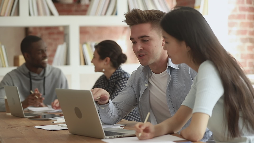 Young male mentor teacher tutor teaching helping asian female classmate intern with online computer project, diverse students talking using laptop explaining course work study together in library | Shutterstock HD Video #1032911279