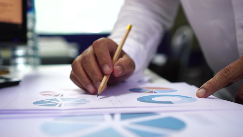 Document report business concept: Businessman manager holding pencil for reading signing in paperwork or documentation files with charts graph marketing showing results successful in corporate office | Shutterstock HD Video #1033029689