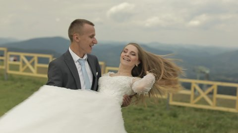Groom holds bride in his arms on a mountain hills. Wedding couple. Happy family. Man and woman in love. Lovely groom and bride. Wedding day. Slow motion