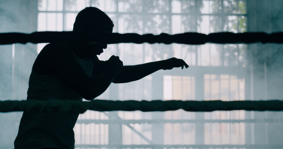 Cinematic slow motion shot of a professional young muscular african man is practicing shadow boxing work out in a ring.
