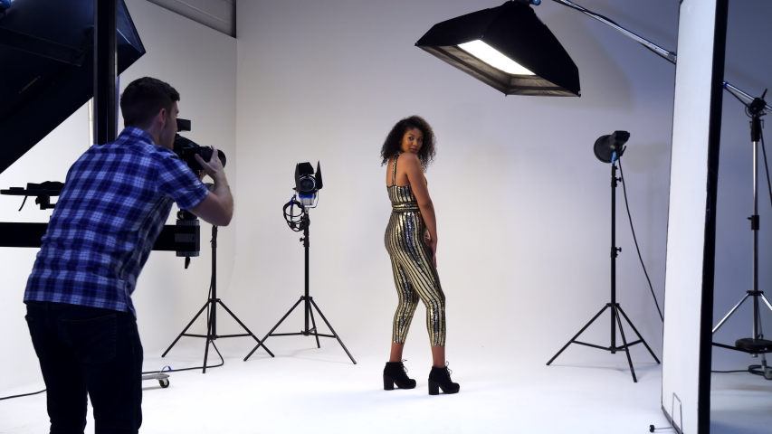 Male Photographer Working With Female Model On Fashion Shoot In Studio  | Shutterstock HD Video #1033121519