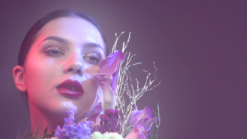 Sexy model girl with fashion bouquet of beautiful flowers. Party. Beauty young woman with design bunch of flowers celebrating in Colorful neon lights, floral art design. Slow motion 4K UHD | Shutterstock HD Video #1033135619