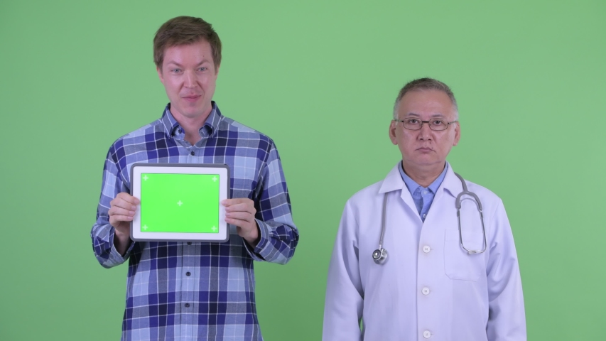 Shocked mature Japanese man doctor with crazy young man showing digital tablet together | Shutterstock HD Video #1033226609