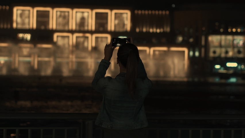 Tourist girl takes photos of the holiday fountains and lights in Dubai | Shutterstock HD Video #1033248749