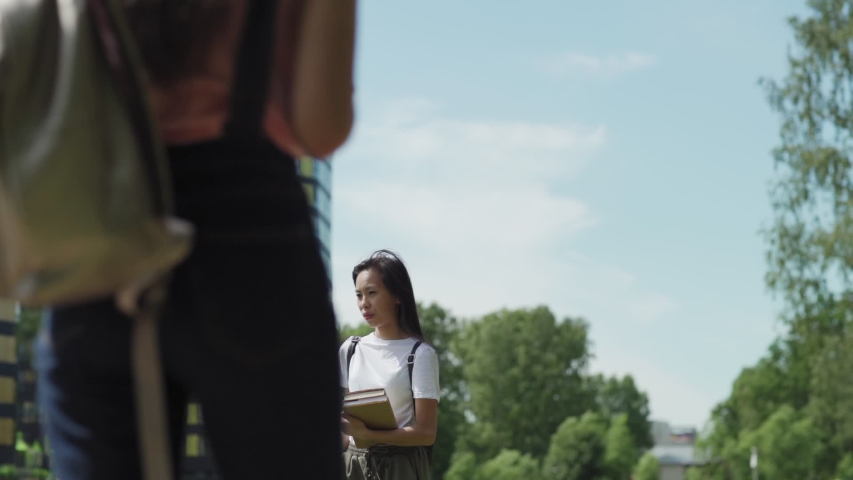 Thoughtful female Asian college student with backpack and textbooks walking on campus after classes, another student passing by her in slow motion | Shutterstock HD Video #1033251569