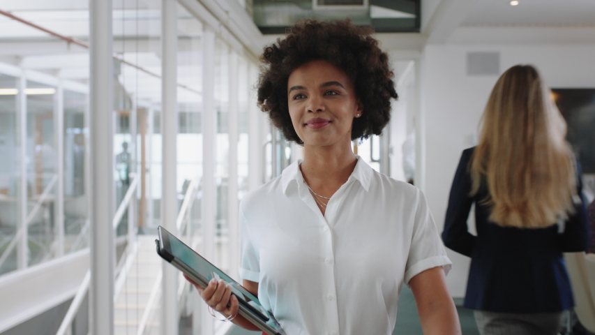 Mixed race business woman smiling walking through office holding tablet computer enjoying successful career in corporate workplace 4k | Shutterstock HD Video #1033257089