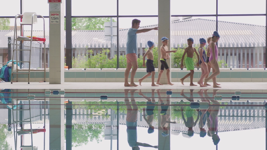 Male Coach Walks Children In Swimming Class Along Edge Of Indoor Pool | Shutterstock HD Video #1033265249