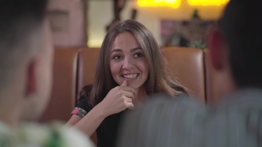 Pretty emotional young woman sitting in the comfortable cafe in front of two guys laughing of their story. Carefree students having fun in the restaurant. Leisure indoors | Shutterstock HD Video #1033297919