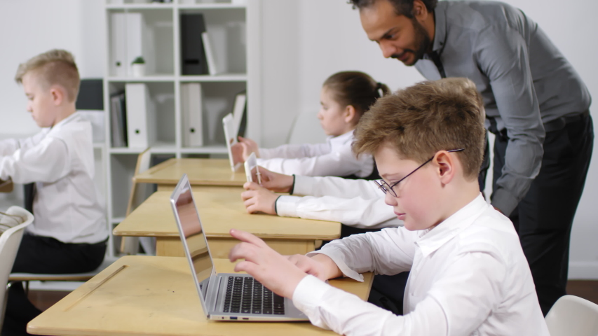 Medium shot of group of preteen Caucasian pupils in school uniform sitting at desks at e-learning lesson and working on laptops and tablets, and Afro-American teacher checking on them and approving | Shutterstock HD Video #1033377239