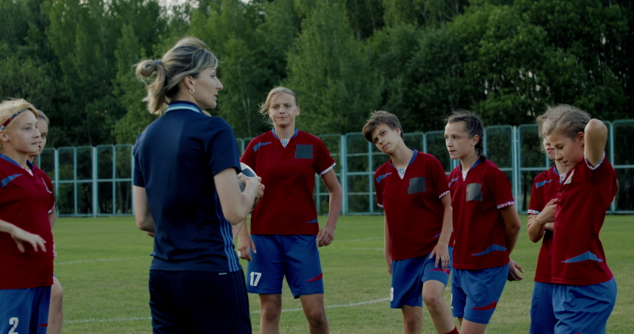 Female coach talking to kids during teenager girl soccer football team practice. 4K UHD 60 FPS SLOW MOTION