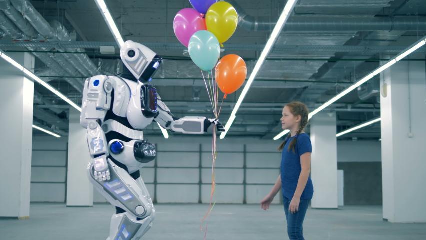 Modern robot gifts balloons to a little girl, side view. | Shutterstock HD Video #1033569719