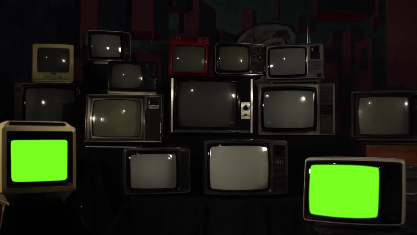 """Two Retro TV Turning On Green Screen over a Pile of Retro TVS from the 80s and 90s. You can replace green screen with the footage or picture you want. You can do it with """"Keying"""" effect. 