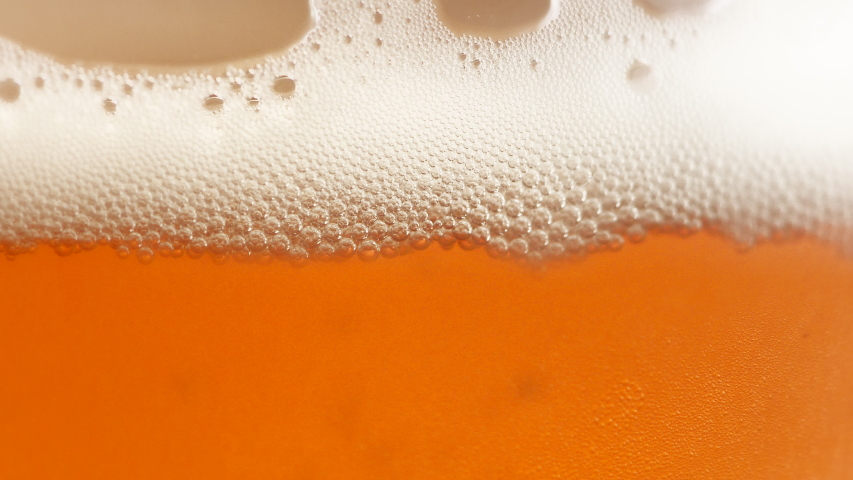 Macro close up of a glass of beer with gorgeous white foam #1033638539