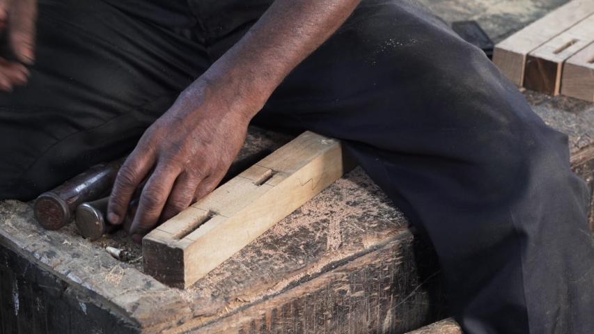 A workman making holes in a wooden piece while using a metal chisel | Shutterstock HD Video #1033654769