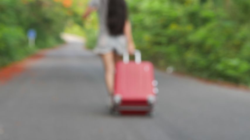 Women tourist with luggage walk  on road. Concept of trip or travel. Video blur.  #1033693319