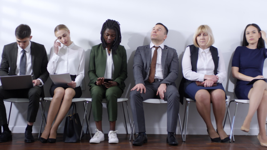 Medium shot of group of people wearing formalwear sitting on chairs and waiting for job interview | Shutterstock HD Video #1033700489