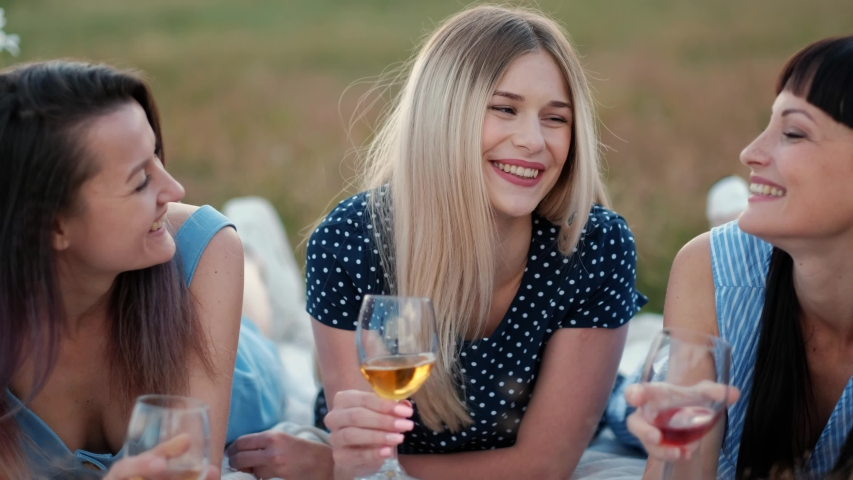 Three young women in blue dresses, and hats lie on plaid and drink wine. Outdoor picnic on grass on beach. Delicious food in picnic basket and wine. Watermelon, grapes and bouquet of daisies. | Shutterstock HD Video #1033706099