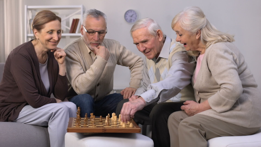 Senior friends playing chess at home, leisure time in good company, togetherness