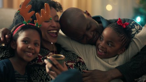 african american family unwrapping christmas presents with children smiling excited little girls enjoying surprise opening gifts mother and father celebrating festive holiday with kids 4k