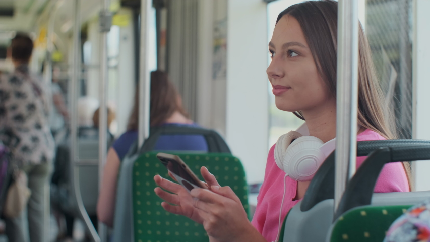 Young stylish woman using public transport, sitting with phone and headphones in the modern tram. | Shutterstock HD Video #1033937219