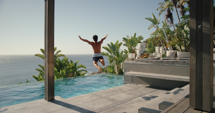 Happy man running jumping in swimming pool at luxury hotel with beautiful ocean view having fun summer vacation enjoying swim at tropical resort on warm sunny day mediterranean travel 4k | Shutterstock HD Video #1034006219