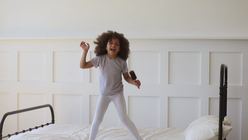 Funny adorable happy kid girl jump on bed sing in hairbrush microphone, cute little african american child having fun dancing to music playing in bedroom alone enjoy pretending singer in the morning