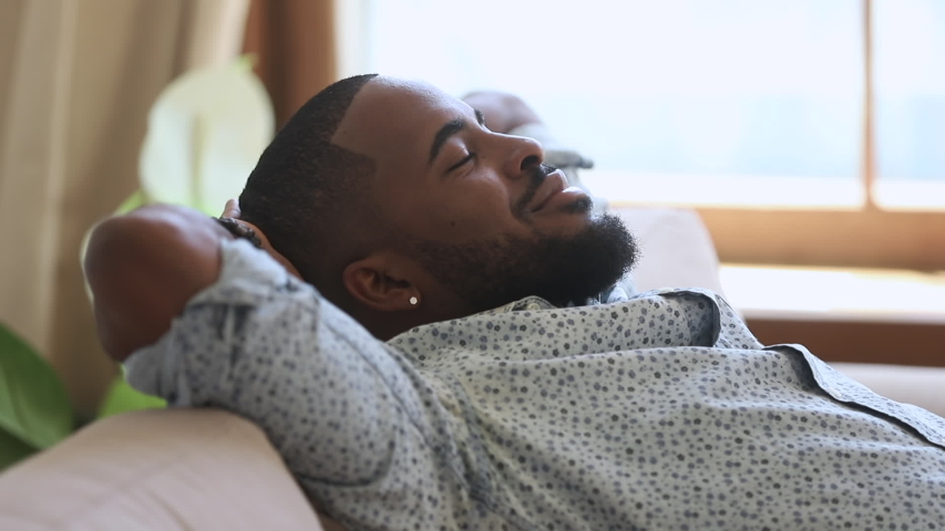 Calm relaxed lazy african american young man resting napping on sofa with eyes closed at home, happy healthy guy breathing fresh air lounge on couch hands behind head enjoy stress free peaceful day | Shutterstock HD Video #1034099249