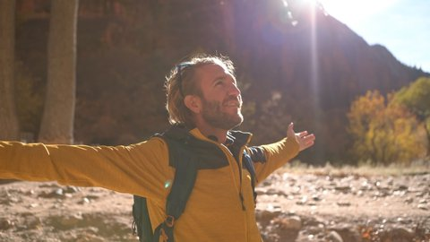 Young man standing in nature arms outstretched by the river in Zion national park in Autumn; hiker male embracing life