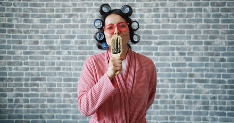 Woman with hair curlers, glasses and bathrobe is singing in hairbrush having fun moving arms standing on brick wall background. People, joy and music concept.