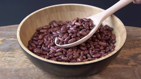 Raw red beans falling into a wooden bowl. Wooden background. Closeup. Food video. Uncooked beans Raw cereal falling into beautiful dishes Macro slow motion.