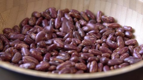 Red beans falling in slow motion over a pile of the same product. Closeup Food video Uncooked beans Raw cereal falling Macro slow motion