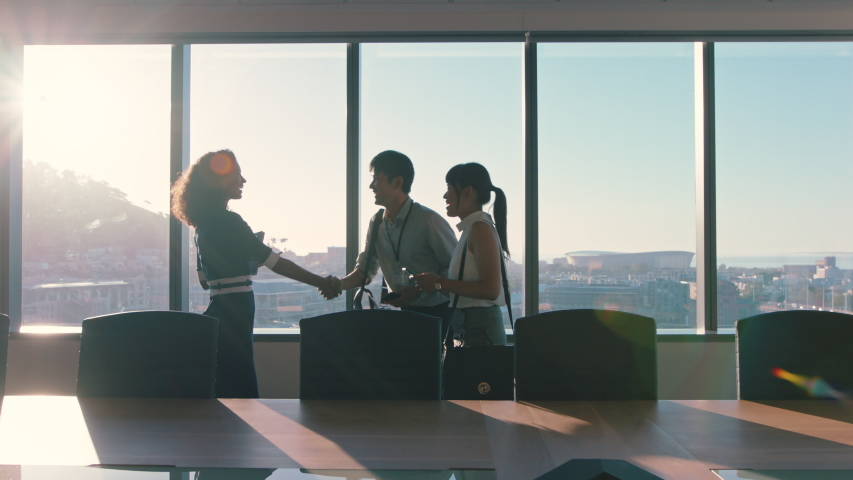 Business people shaking hands consultant greeting international clients with handshake planning partnership deal female executive meeting shareholders in corporate office at sunset | Shutterstock HD Video #1034474609