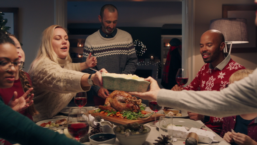 Family christmas dinner man cutting turkey serving delicious meal at festive celebration people sitting at table enjoying delicious feast celebrating holiday at home 4k footage | Shutterstock HD Video #1034495699