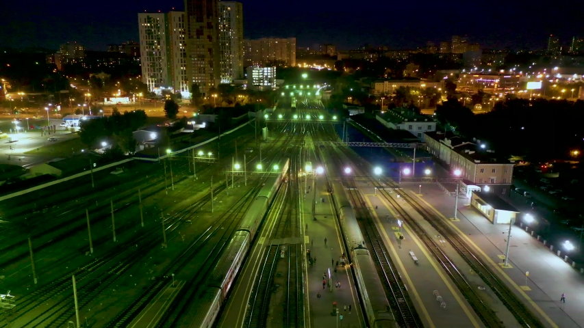 Aerial night view of train station, trains slowly moving from platforms, cars driving on streets, pedestrians walking on platforms. 4K footage from drone | Shutterstock HD Video #1034531669