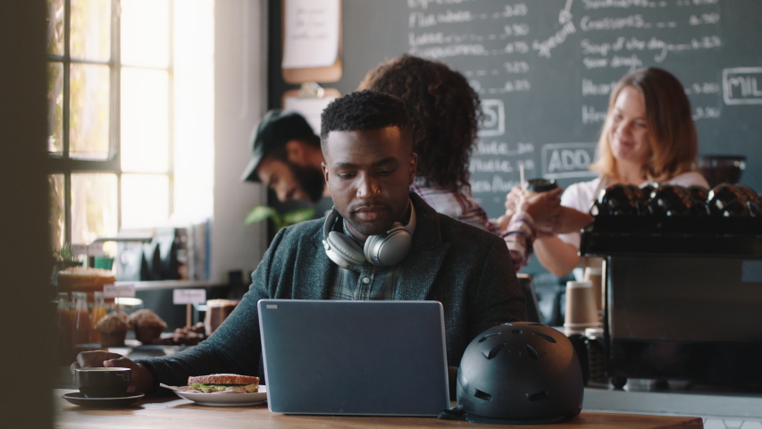 Young african american man using laptop in cafe browsing online listening to music wearing headphones enjoying mobile computer technology | Shutterstock HD Video #1034534399