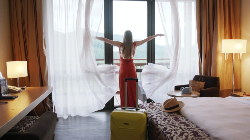 Shot back young woman is entering opening curtain lace hands raise standing in luxury apartment inspecting space feel happy apartment tourist trip holiday close up slow motion | Shutterstock HD Video #1034581439