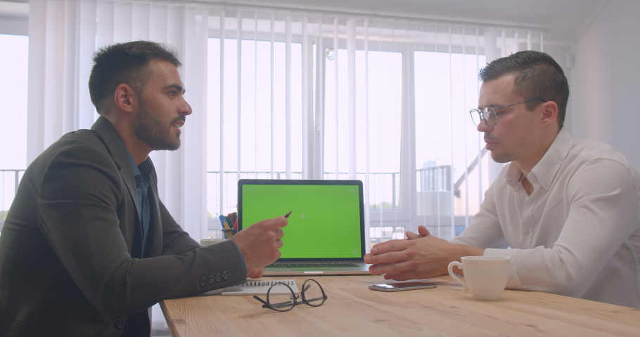 Portrait of two adult successful businessmen having a formal discussion with laptop with green screen in the office indoors on the workplace | Shutterstock HD Video #1034636189