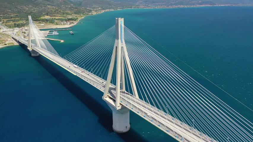 Aerial drone video of world famous cable suspension bridge of Rio - Antirio Harilaos Trikoupis, crossing Corinthian Gulf, mainland Greece to Peloponnese, Patras | Shutterstock HD Video #1034699699