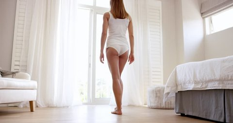 Attractive young woman opening curtains in luxury home stretching at window wearing white underwear